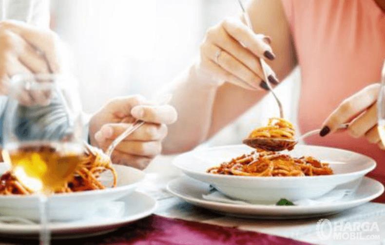 Gambar ini menunjukkan 2 orang sedang makan makanan