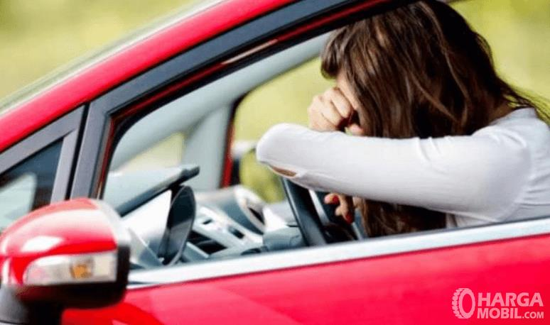 Gambar ini menunjukkan seorang wanita sedang mengantuk di dalam mobil
