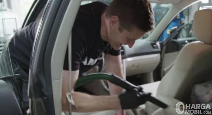 Gambar ini menunjukkan seorang pria membersihkan kain mobil dengan vacuum cleaner