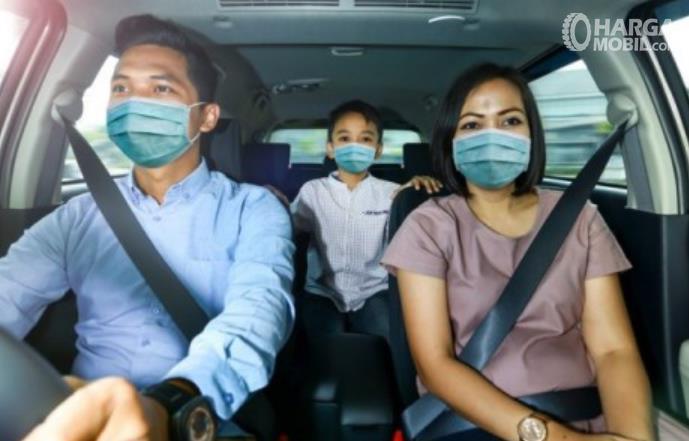 Gambar ini menunjukkan 3 orang di dalam mobil pakai masker