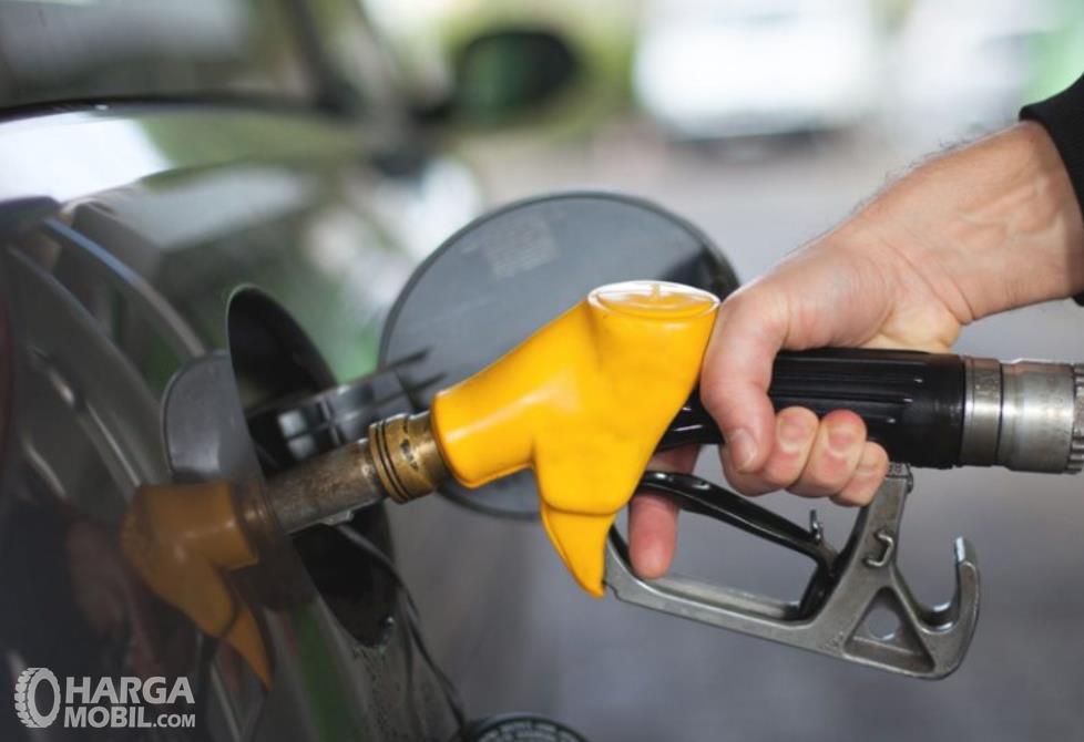 Gsmbsr ini menunjukkan sebuah tangan memegang alat pengisi bahan bakar warna kuning
