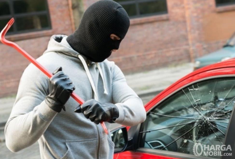 Gambar ini menunjukkan seorang bertopeng memecahkan kaca mobil dengan besi