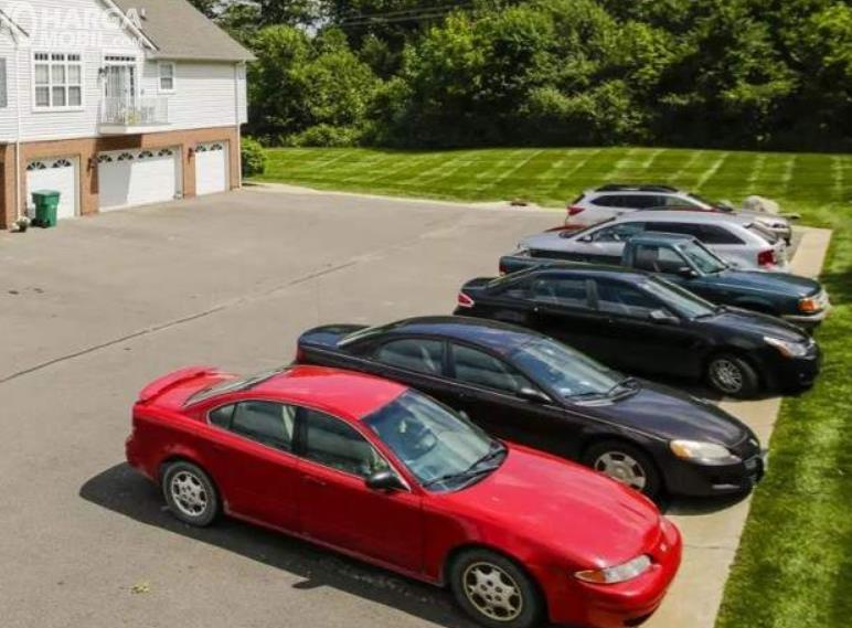 Gambar ini menunjukkan beberapa mobil parkir di luar rumah