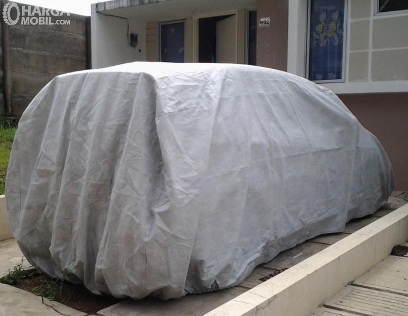 Gambar ini menunjukkan mobil yang diparkir di depan rumah tertutup cover