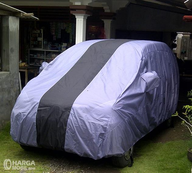 Gambar ini menunjukkan mobil yang ditutup cover berwarna