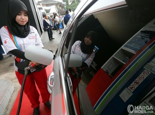Gambar ini menunjukkan seorang wanita mengisi bahan bakar pada mobil
