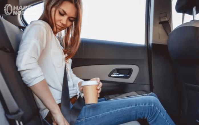 Gambar ini menunjukkan seorang wanita memasang sabuk pengaman di jok baris belakang