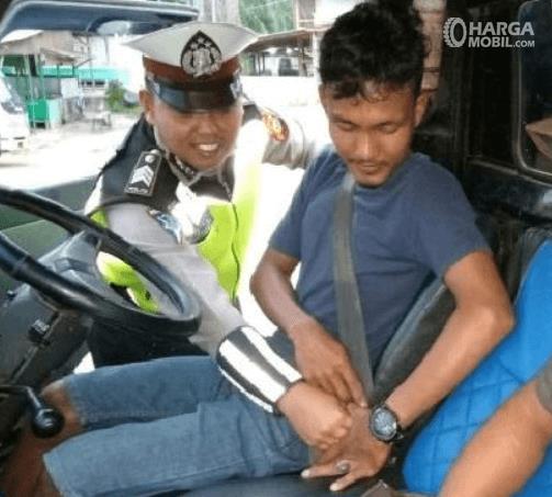 Gambar ini menunjukkan seorang polisi membantu pengemudi memasang sabuk pengaman