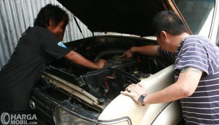 Gambar ini menunjukkan 2 orang sedang melihat mesin mobil