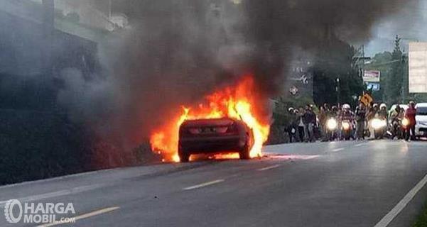 Gambar ini menunjukkan mobil terbakar dan terdapat beberapa orang yang antri