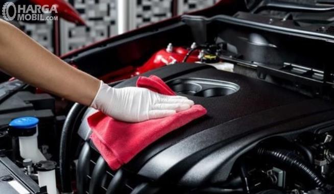 Gambar ini menunjukkan sebuah tangan memegang kain bersihkan mesin mobil