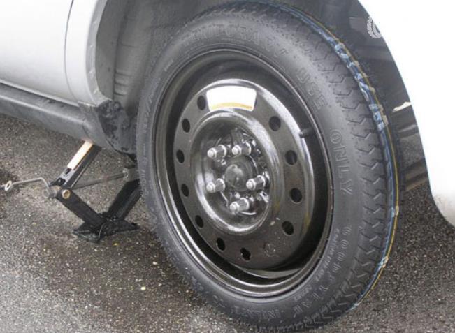 Gambar ini menunjukkan ban cadangan dipasangkan pada mobil