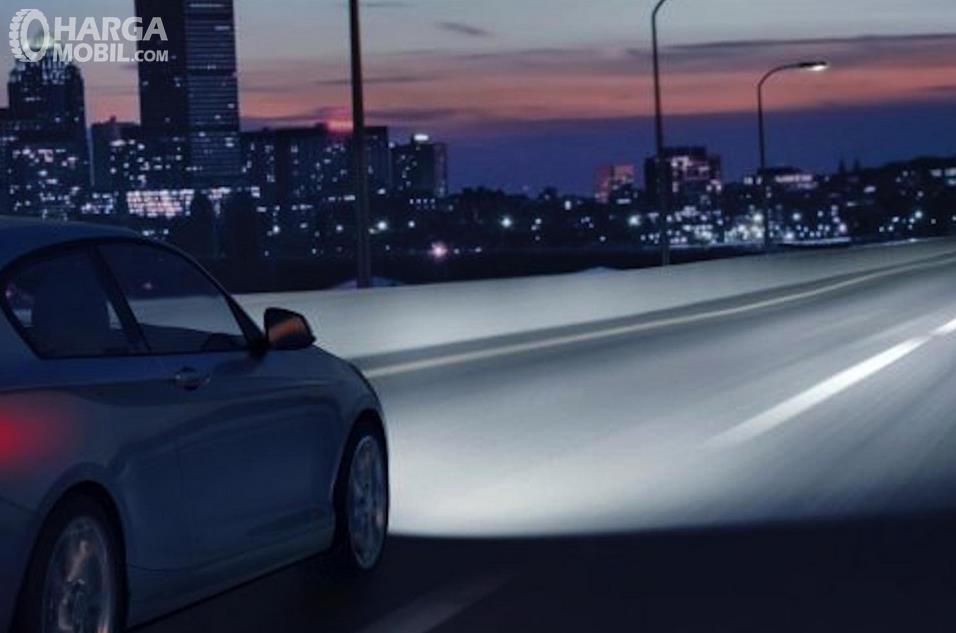 Gambar ini menunjukkan cahaya dari lampu jauh pada mobil di jalan gelap