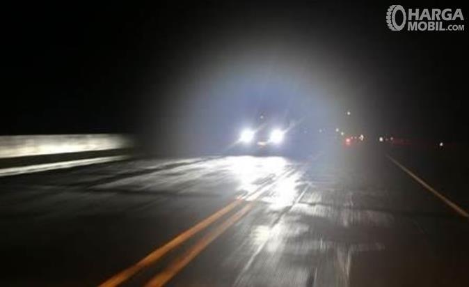 Gambar ini menunjukkan mobil dengan menyalakan lampu jauh