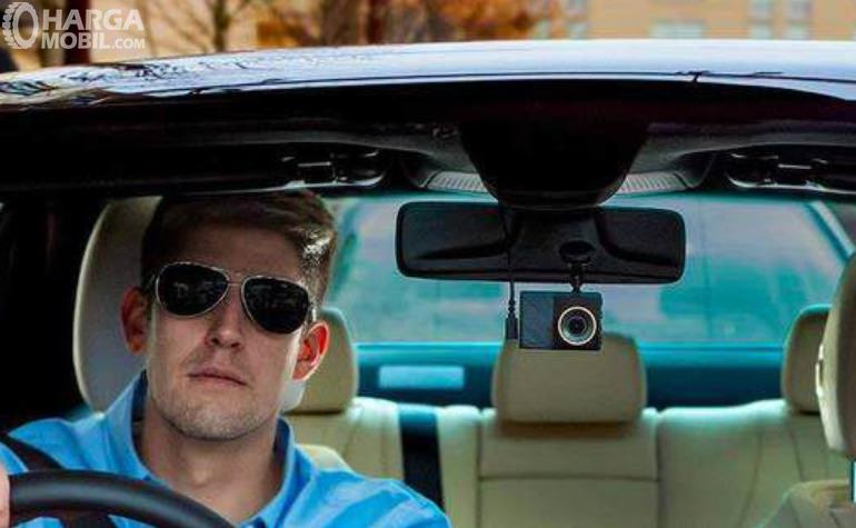 Gambar ini menunjukkan seorang pria sedang mengemudi mobil dengan kacamata