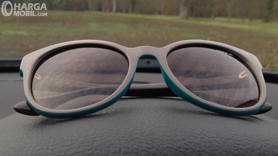Gambar ini menunjukkan kacamata diletakkan di atas dashboarad mobil