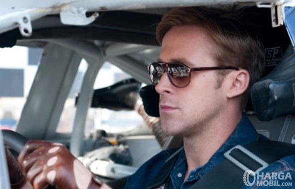 Gambar ini menunjukkan seorang pengemudi memakai kacamata hitam