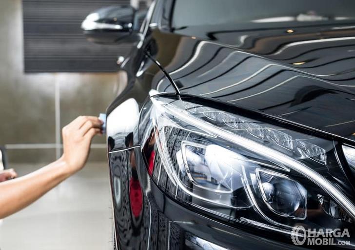 Gambar ini menunjukkan sebuah tangan sedang coating bodi mobil hitam