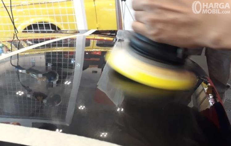 Gambar ini menunjukkan mobil warna hitam sedang dipoles