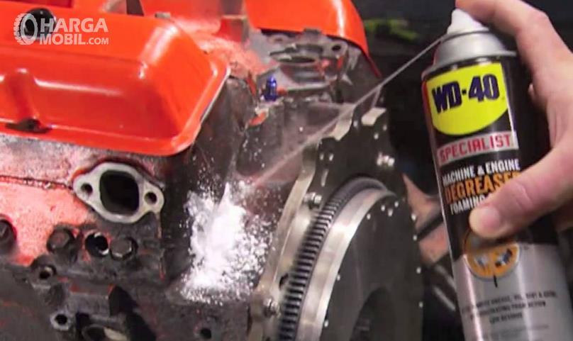 Gambar ini menunjukkan cairan engine degreaser sedang disemprotkan bagian mesin mobil