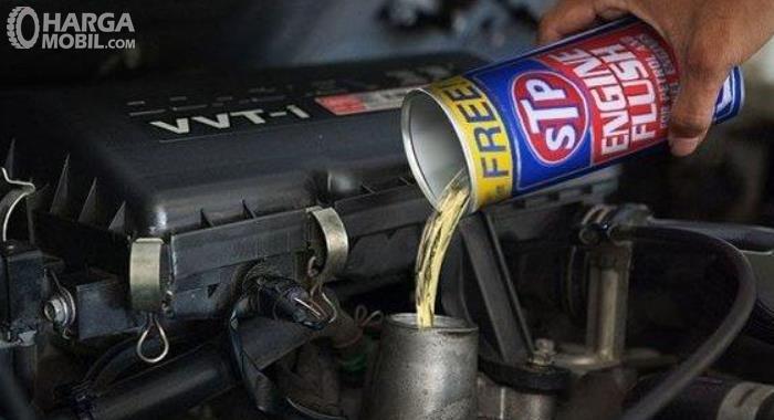 Gambar ini menunjukkan cairan engine flush dimasukkan ke dalam mesin mobil