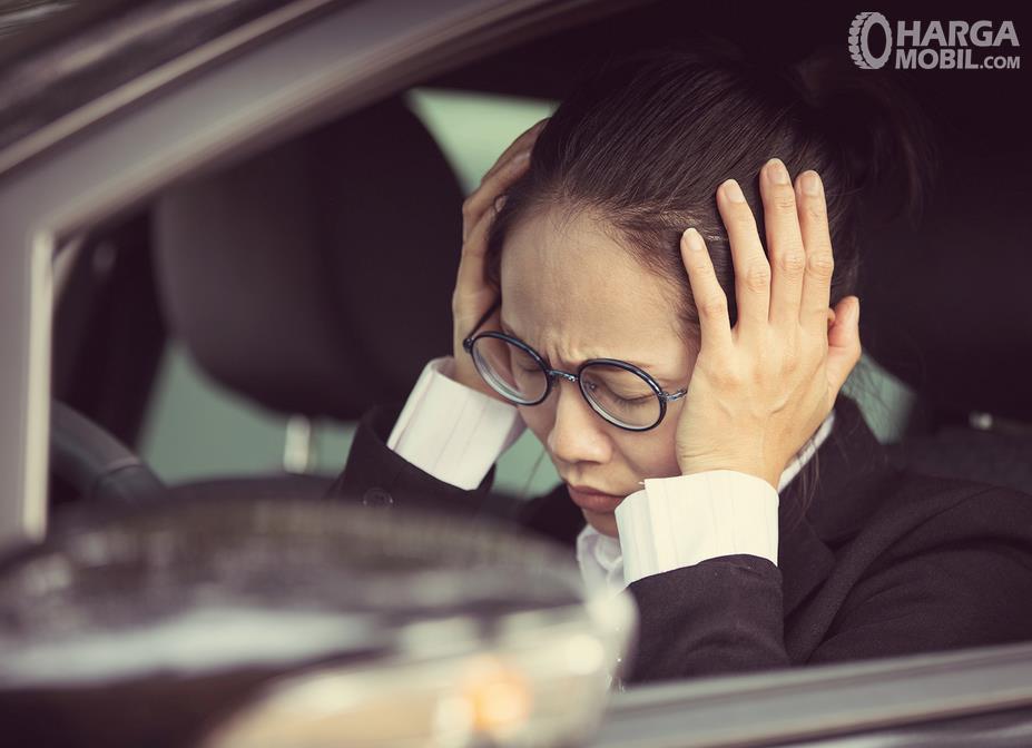 Gambar ini menunjukkan seorang wanita merasa pusing di dalam mobil
