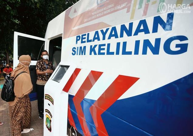 Gambar ini menunjukkan Pelayanan SIM Keliling dan 2 orang sedang berdiri