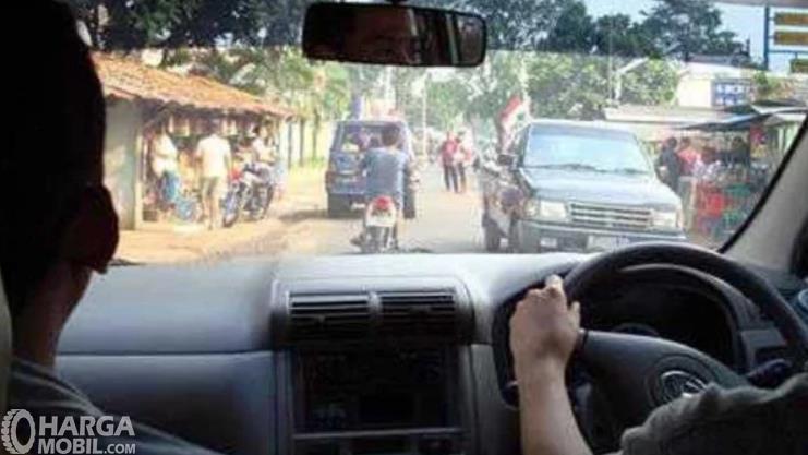Gambar ini menunjukkan pengemudi dan penumpang depan berada di mobil