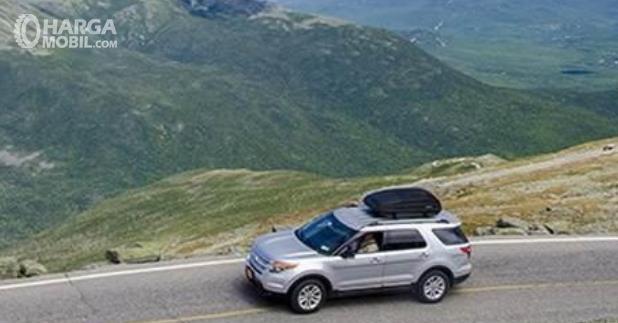 Gambar ini menunjukkan mobil melaju di jalan daerah pegunungan