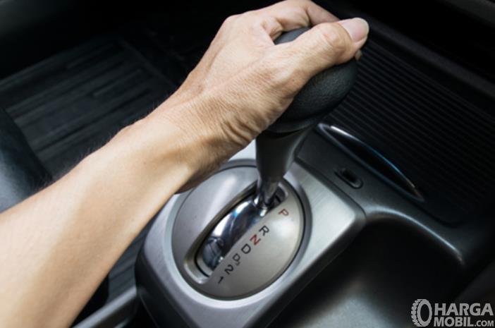 Gambar ini menunjukkan sebuah tangan memegang tuas transmisi mobil matic