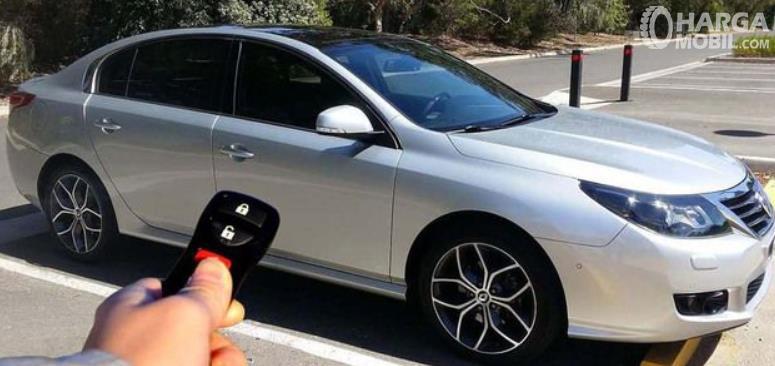 Gambar ini menunjukkan sebuah tangan memegang remote keylees entry system mobil