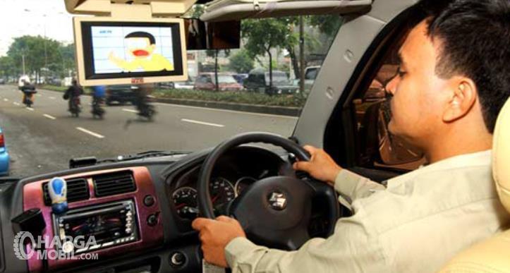 Gambar ini menunjukkan seorang pengemudi dan ada layar di atap