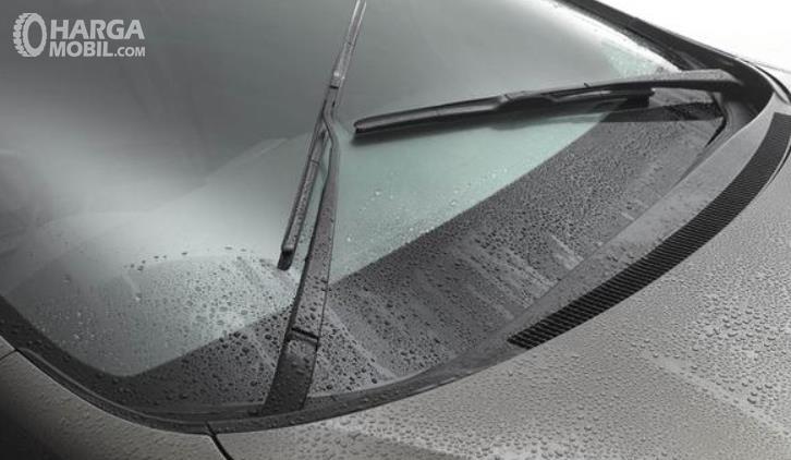 Gambar ini menunjukkan kaca mobil depan dan wiper dalam kondisi basah