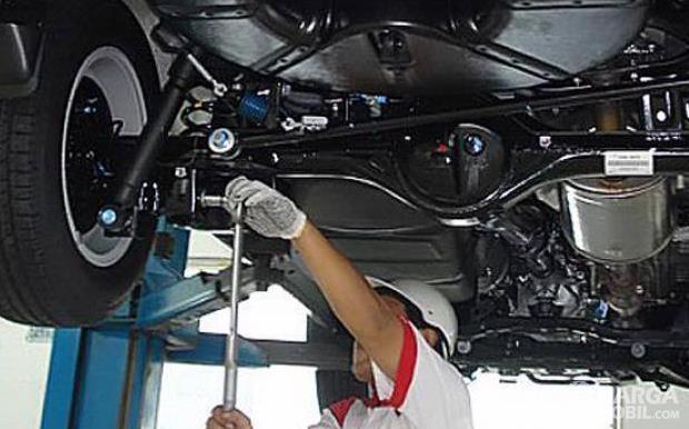 Gambar ini menunjukkan seorang mekanik mengecek kaki-kaki mobil
