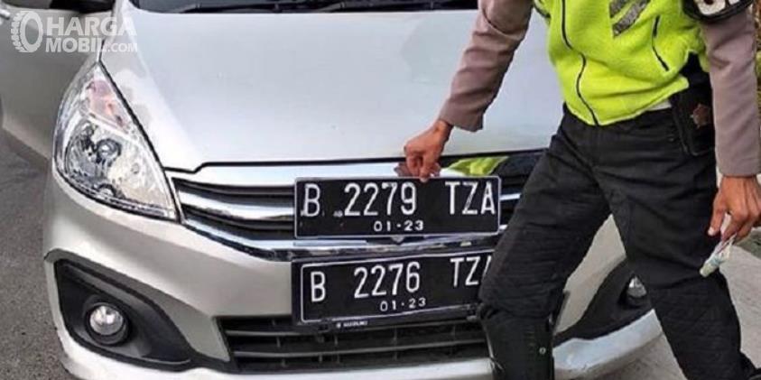Gambar ini menunjukkan seorang polisi memegang plat nomor
