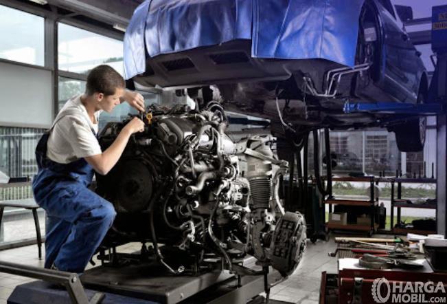 Gambar ini menunjukkan seorang mekanik memeriksa mesin yang dilepas dari mobil