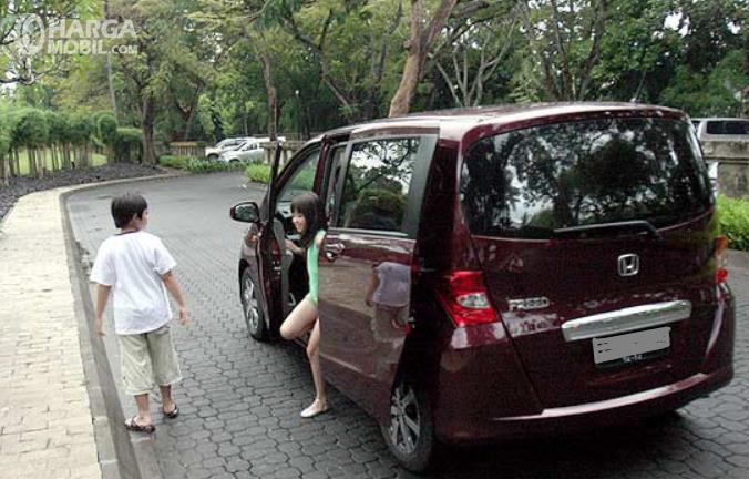Gambar ini menunjukkan anak-anak sedang keluar mobil pintu geser