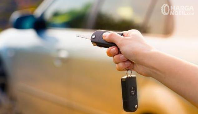 Gambar ini menunjukkan sebuah tangan memegang remote mobil