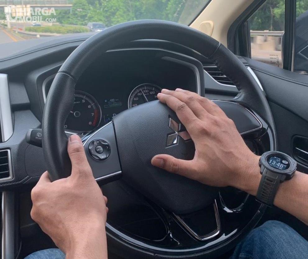 Gambar ini menunjukkan 2 buah tangan memegang kemudi dan menekan klakson