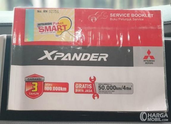 Gambar ini menunjukkan buku pedoman pemilik dan Servis Booklet Mitsubishi Xpander