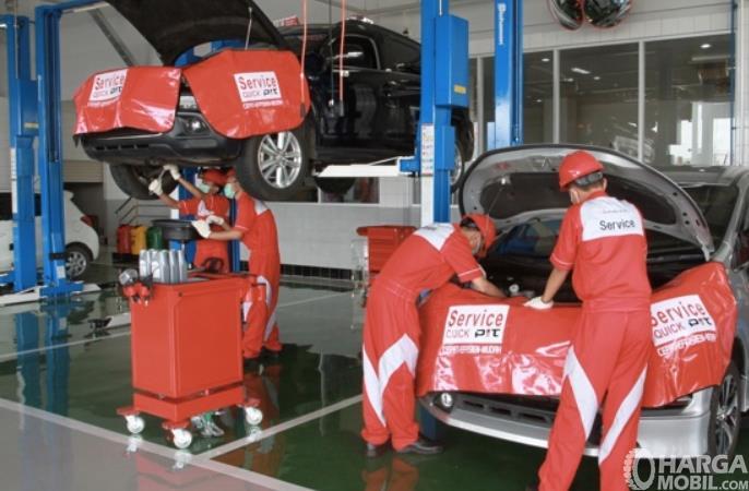 Gambar ini menunjukkan beberapa mekanik servis mobil Mitsubishi