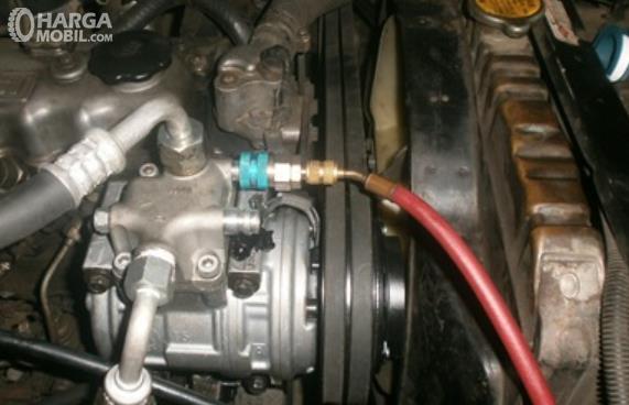 Gambar ini menunjukkan kompresor AC pada mobil
