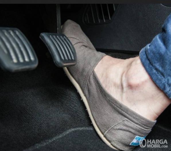 Gambar ini menunjukkan kaki menekan pedal gas pada mobil
