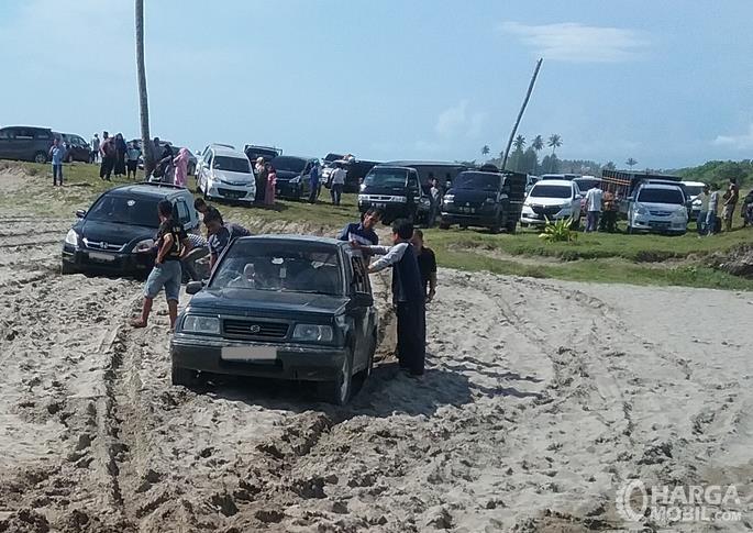 Gambar ini menunjukkan 2 mobil terjebak di lumpur