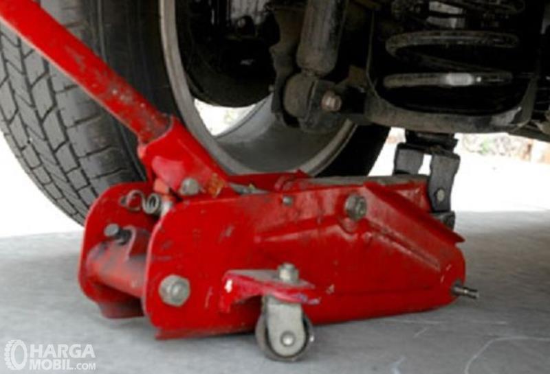 Gambar ini menunjukkan dongkrak mobil warna merah sedang dipakai untuk mengongkrak