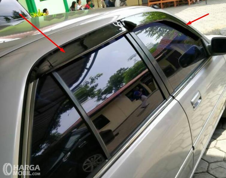 Gambar ini menunjukkan talang air pada mobil ditunjuk panah merah