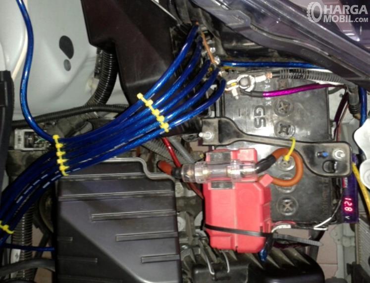 Gambar ini menunjukkan mesin Honda Brio dengan kabel Grounding warna biru