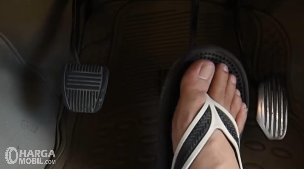 Gambar ini menunjukkan sebuah kaki menekan pedal rem mobil