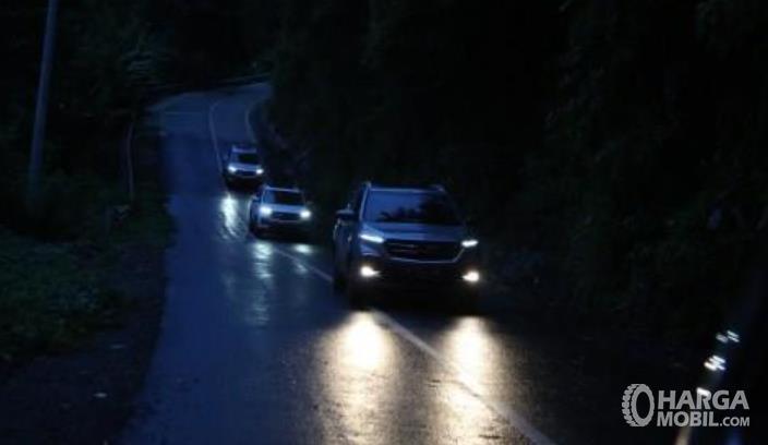 Gambar ini menunjukkan beberapa mobil melaju di jalanan yang menurun