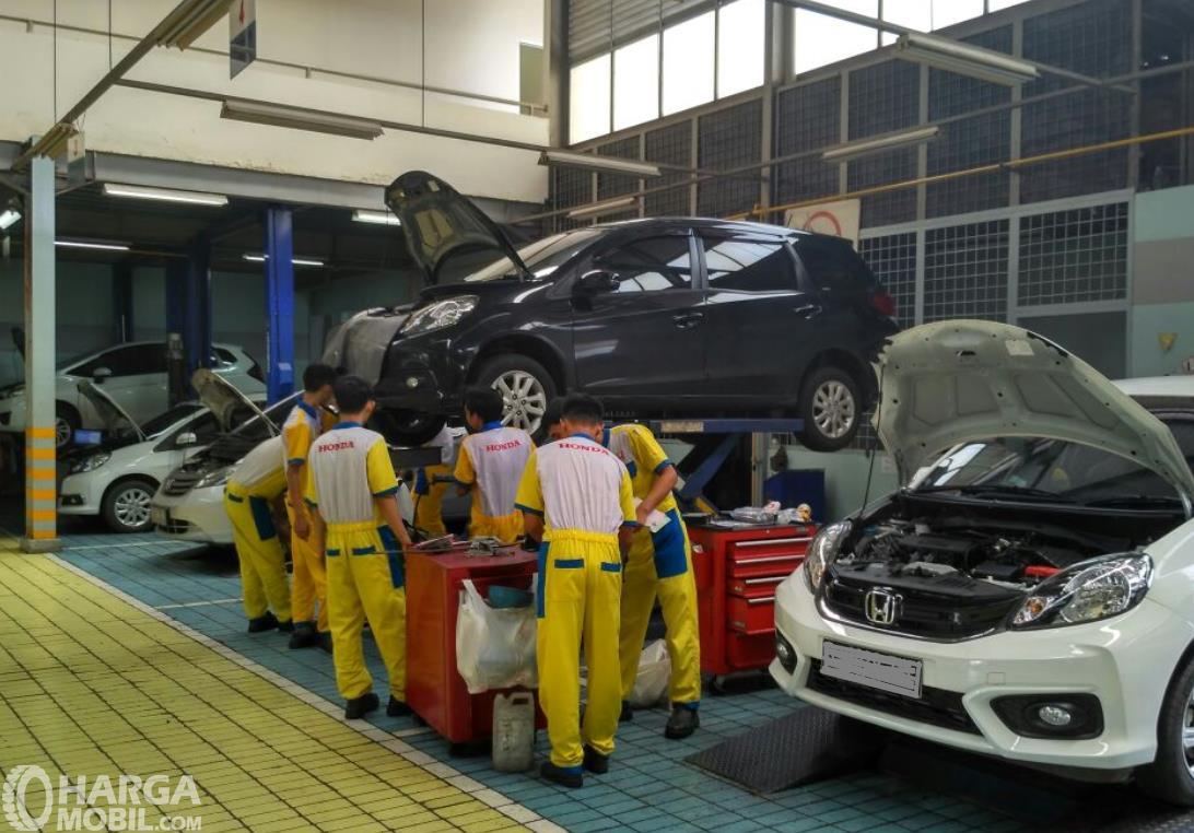 Gambar ini menunjukkan banyak mekanik sedang melakukan servis mobil